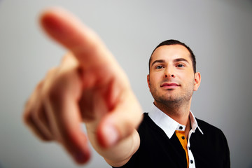 Young man pointing on something over gray background