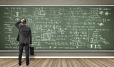Mann steht vor Wandtafel mit vielen Formeln