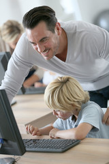 Teacher with school boy in computers's lab