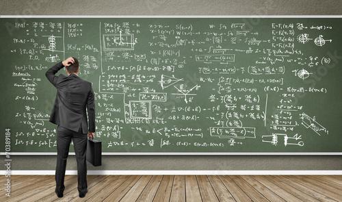 Mann steht vor Wandtafel mit vielen Formeln - 70389184