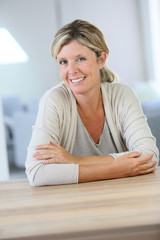 Portrait of smiling confident woman sitting at table