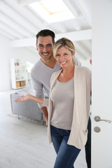 Cheerful mature couple standing at home front door