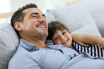 Daddy with little girl relaxing in sofa