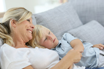 Mother and little boy relaxing in sofa