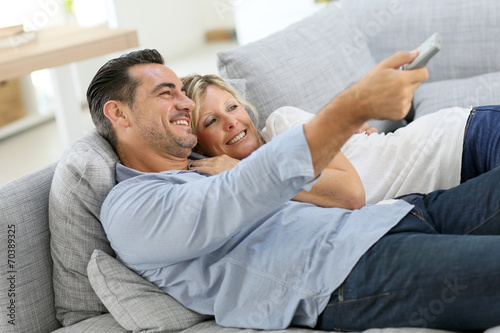 Middle-aged couple in sofa watching tv - 70389325
