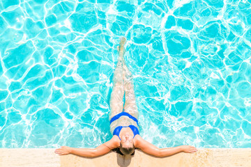 woman relaxes at the edge of the pool