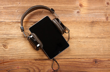 Tablet with headphones on old wooden desk.