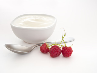 Natural yoghourt, yoghurt with raspberries and spoon over white