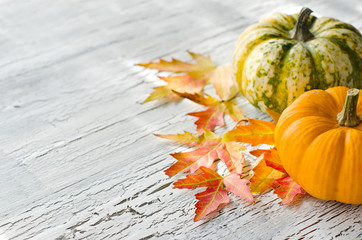 Pumpkins on wooden background with autumn leaves