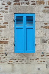 Window closed by blue shutters detail of a home in Brittany