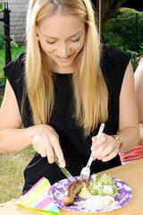 Frau isst Bratwurst und Salat auf Gartenfest