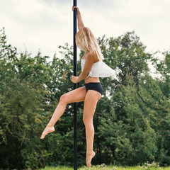 Sensual woman pole dancer performing outdoors in a park.