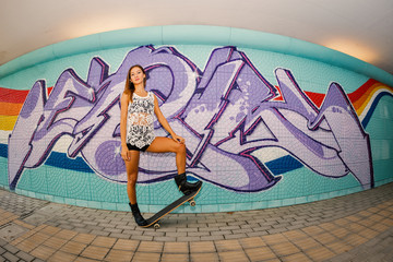 Teenager with skateboard full body portrait against murals wall.