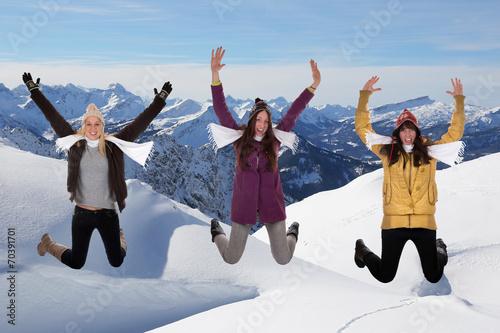 canvas print picture Junge Frauen springen im Winter in den Bergen im Schnee