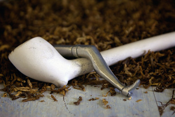 clay pipe with tobacco and tamper