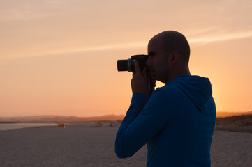 Young man taking photos in the beach at sunset