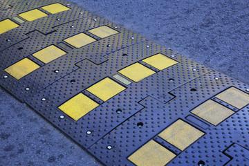 A yellow stripe speed ramp on an asphalt road.