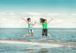 Two happy women jumping in the water of sea