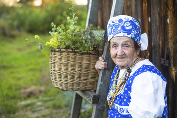 Old smiling woman in traditional clothes in the countryside.