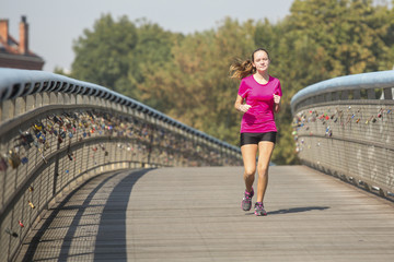 Happy cute girl fitness model runner working out jogging.
