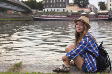 Young cute girl sitting on a stone embankment of river.