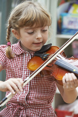 Young Girl At School Learning To Play Violin
