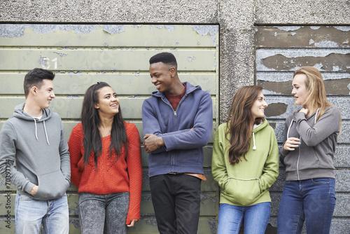 Fototapeta Gang Of Teenagers Hanging Out In Urban Environment
