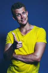 Emotive portrait of happy young blonde man in yellow t-shirt ove