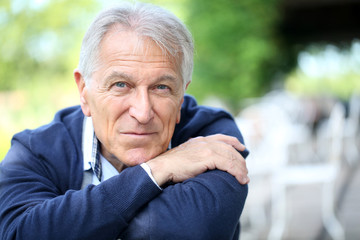Portrait of senior man sitting in home garden