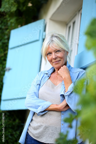canvas print picture Senior woman standing outside the house