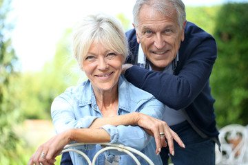 Portrait of cheerful senior couple in home garden