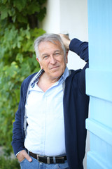 Senior man leaning on wall outside the house