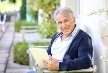 Senior man websurfing on tablet outside the house
