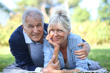 Senior couple relaxing in park laid on grass