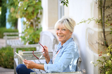 Senior woman relaxing outside and using tablet