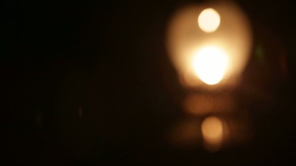 Old oil lamp smoldering in the darkness with focus changing