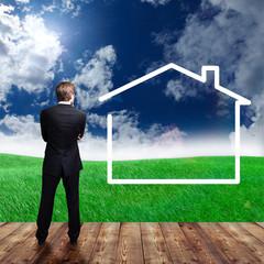 Geschäftsmann vor leerer Wiese mit Einfamilienhaus-Symbol