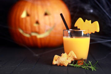 Glass of orange juice decorated for Halloween