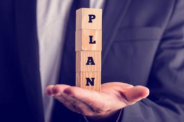 Businessman holding blocks reading - Plan