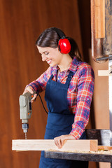 Female Carpenter Drilling Wood In Bandsaw