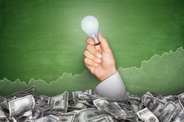 Pile of dollar bills on blackboard with hand holding light bulb