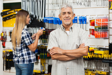 Confident Senior Man With Arms Crossed In Hardware Store