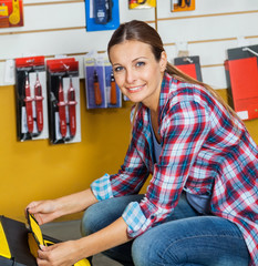 Smiling Woman Analyzing Tool Case In Store
