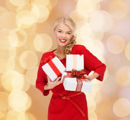 smiling woman in red dress with gift boxes