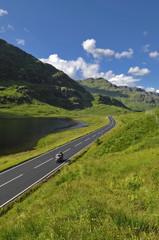 Speeding motorbike on mountain road in Scotland