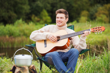 smiling man with guitar and dixie in camping