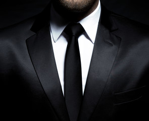 Man gentleman in black suit and tie