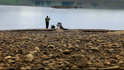 man fishing at reservoir uk