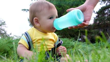 Cute little baby boy drinking water from feeding bottle outdoors