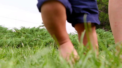 Cute baby boy making his first steps on grass